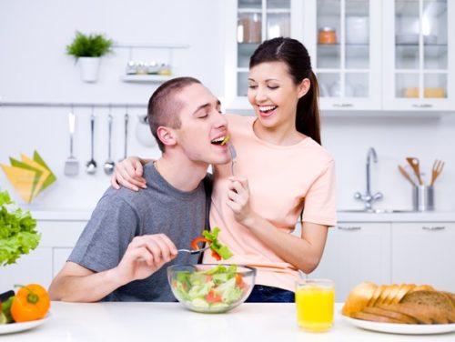 женщина кормит мужчину салатом